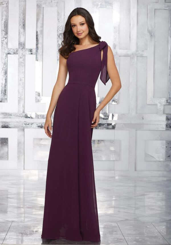 Mori Lee bridesmaid dress style number 21539. One Shoulder Chiffon Bridesmaids Dress Features a Removable Shoulder Bow and Flowy A-line Silhouette. Shown in Eggplant.