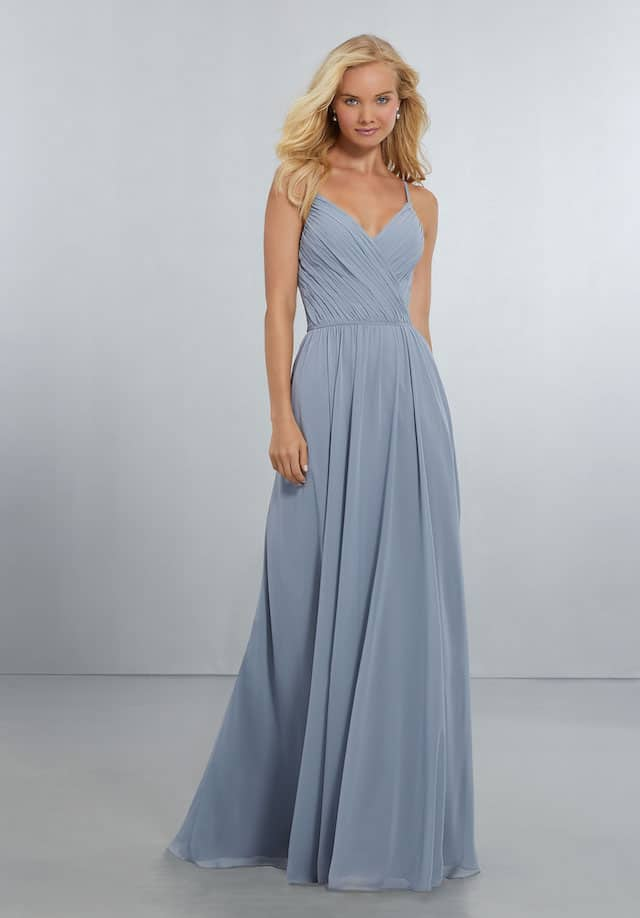 Mori Lee bridesmaid dress style number 21556. Surplus V-Neckline with Spaghetti Straps on a Flowing Chiffon Gown. Open, V-Back with Crystal Button Detail and Zipper Back. Shown in Dove.