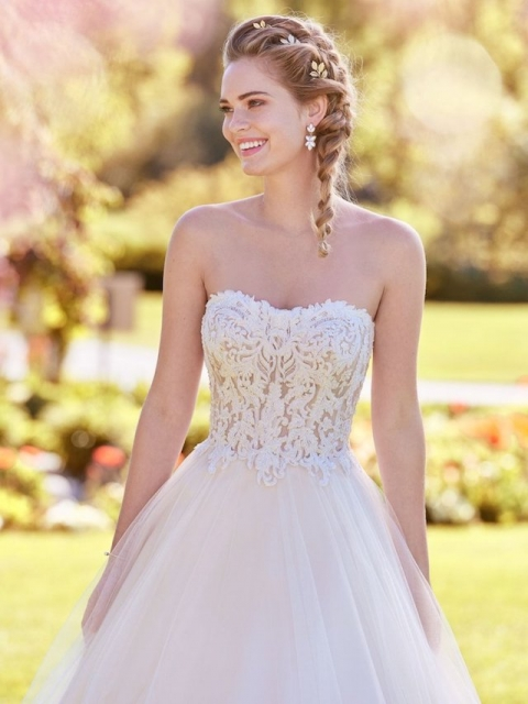 The Lavonne is a princess-style wedding dress by Rebecca Ingram. It features a sheer bodice that is accented in exposed boning and beaded lace motifs. The tulle ballgown skirt and strapless scoop neckline completes the dress. Call Runway Bridal at 613-966-0122 to book your appointment!