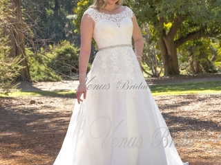 The Amaya wedding dress by Venus Bridal is a lace illusion gown featuring a bateau neckline and fitted bodice over satin with cap sleeves. The Amaya is highlighted with a beaded waist and illusion back. Call Runway Bridal in Belleville, Ontario today at 613-966-0122 to book your appointment!